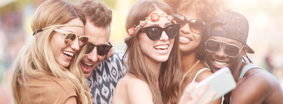 young adults smiling for selfie at music festival