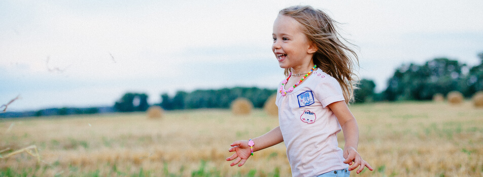 Young child with blonde hair running in the field happy