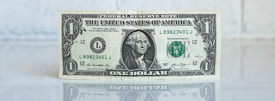 A green dollar bill with George Washington's face sits upright against a white brick wall reflects on a clear counter