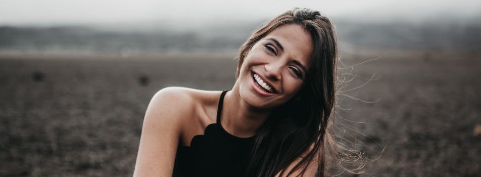 Brunette woman. wearing a black tank top smiles while leaning her head to one side and sitting in a dirt field