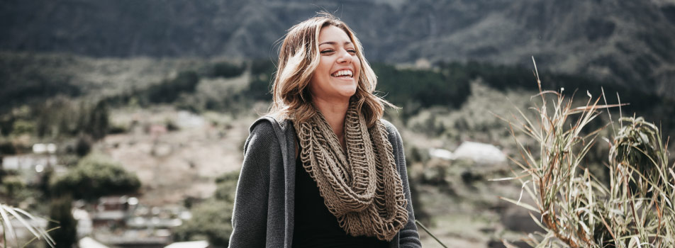 Brunette woman wearing a beige scarf smiles with healthy gums as she stands at the foot of a mountain