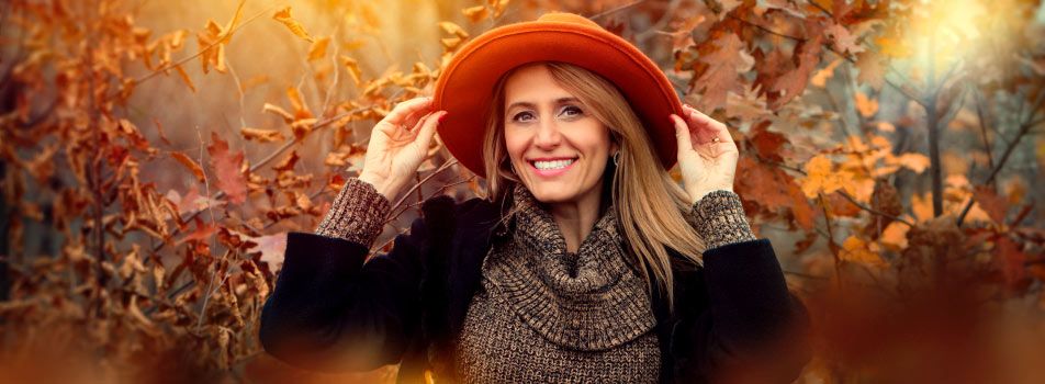Blonde middle-aged woman wearing a black sweater and rust-colored hat smiles with dentures in the fall leaves
