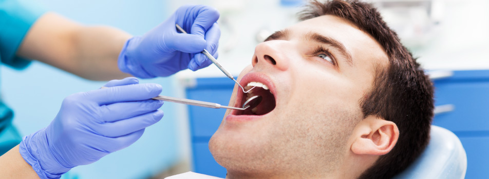 Brunette man gets his teeth professionally cleaned by a dental hygienist at Southwest Smiles Family Dentistry