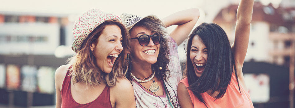 3 female friends smile brightly with tooth-colored fillings on a summer day outside