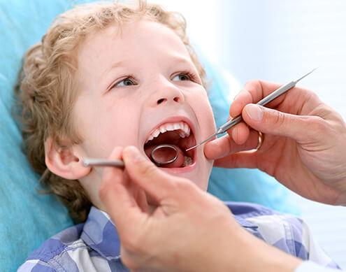 young boy having his teeth examined