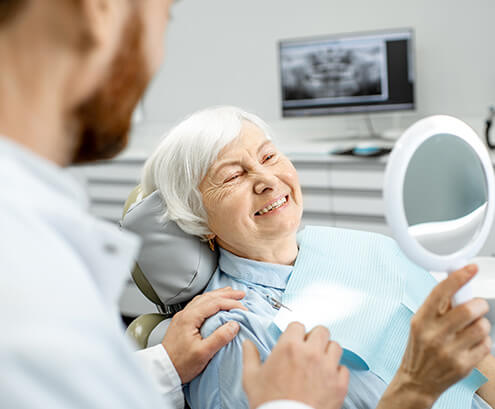 smiling senior woman sitting in a dental chair