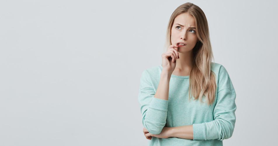 Blonde woman in a mint shirt bites her lip and wonders how to cope with dental anxiety