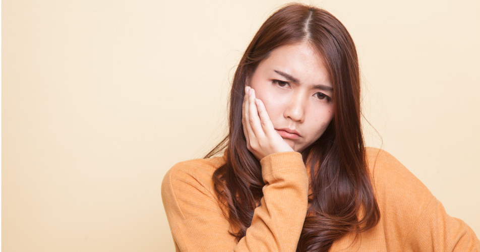 Brunette woman in a yellow shirt cringes in pain due to a toothache from a sinus infection