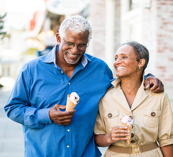 man and woman walking with ice cream