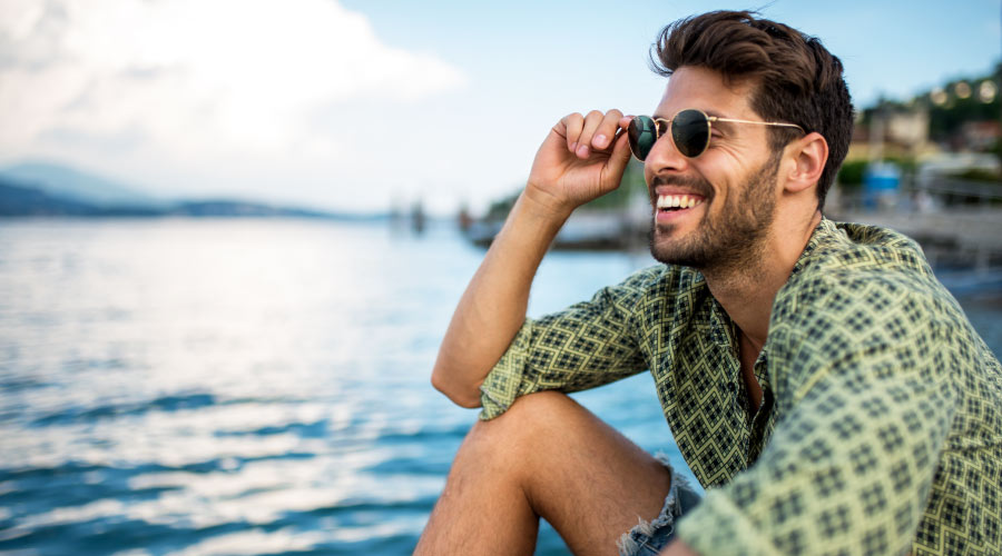 Brunette man wearing a green shirt and sunglasses smiles by the lake with healthier gums in Austin, TX