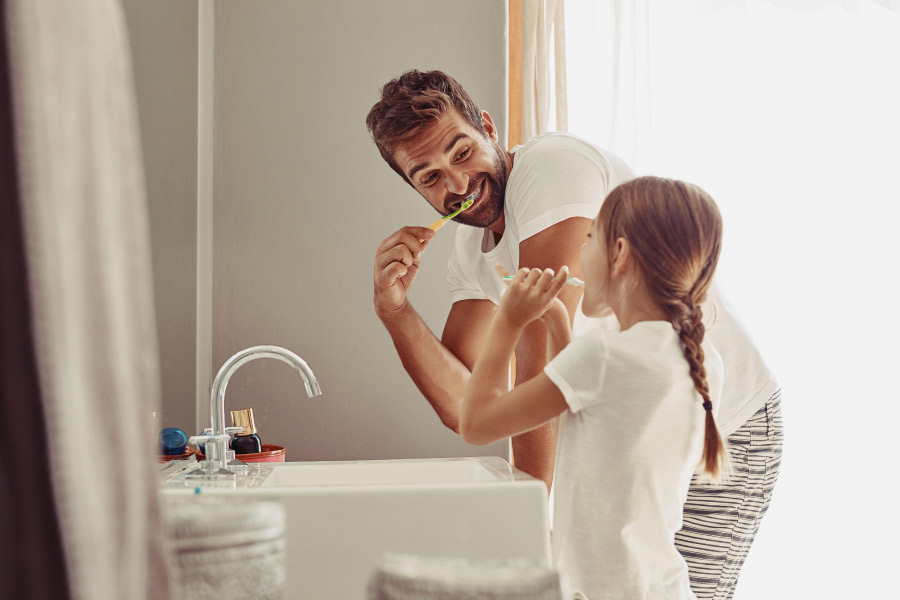 Daddy and daughter brush their teeth together in the bathroom to make brushing fun
