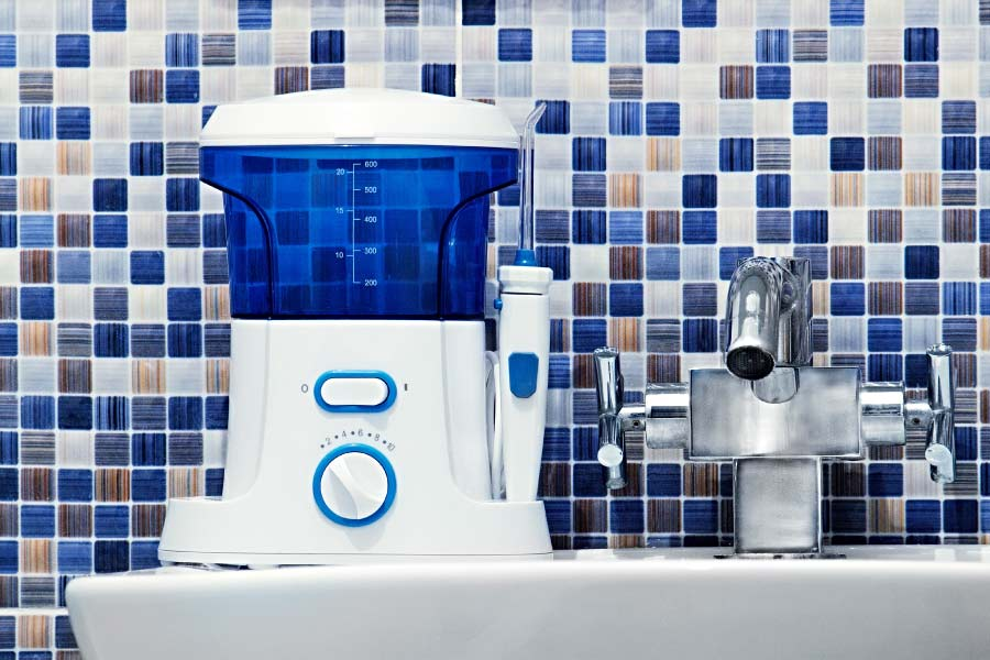 A blue and white water flosser sits on the bathroom counter against an attractive blue and white backsplash