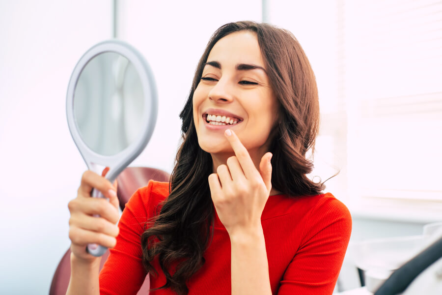 Brunette woman in a red shirt smiles in a mirror with her new dentures