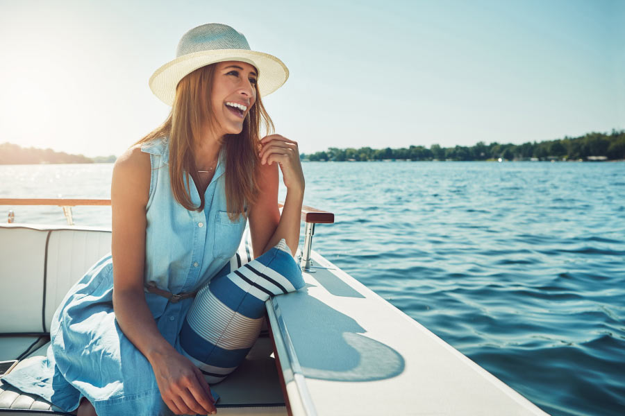 Happy woman with a dental crown smiles while boating on the lake in Austin, TX