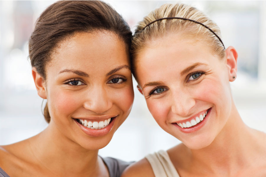 Two women smile in South Austin after improving their smiles with cosmetic dentistry at Southwest Smiles