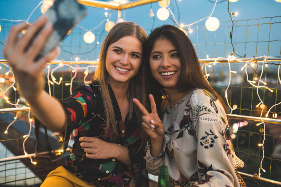 A blonde and a brunette woman smile like celebrities while taking a selfie in front of twinkle lights