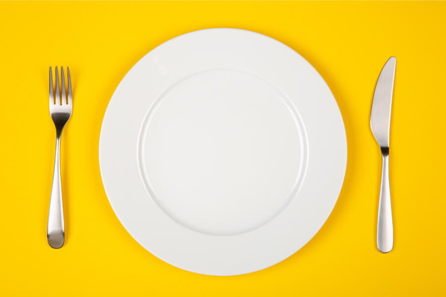Aerial view of an empty plate with a knife and fork on a yellow table that can fit foods that are good for teeth