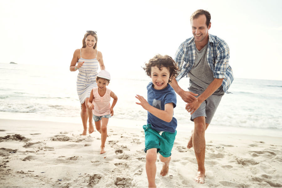 Mom and dad run along a beach with their children, who have great oral health and overall health