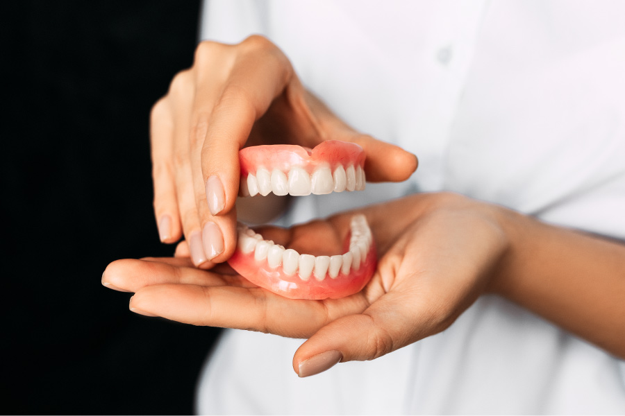 A dentist holds a pair of full dentures in their hands as an affordable tooth replacement in Austin, TX