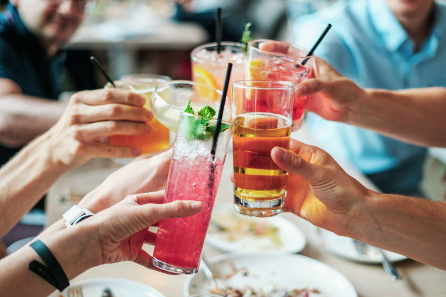 A group of people touch their alcohol drinks together at the table