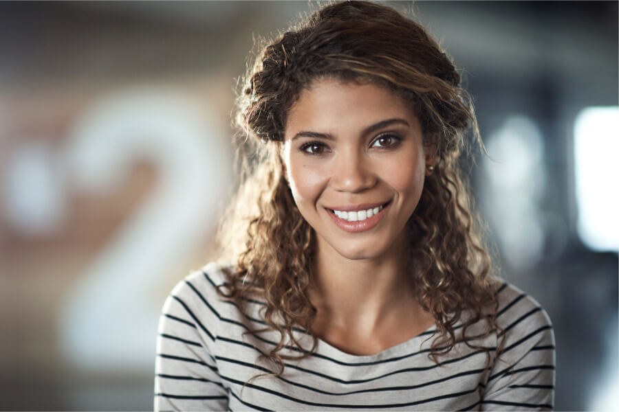 Curly-haired brunette woman in a striped shirt smiles after professional teeth whitening in Austin, TX